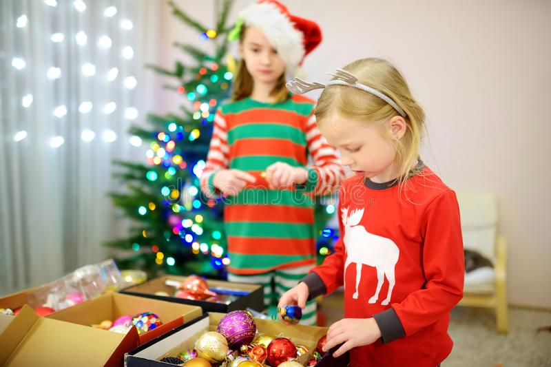 Two adorable sisters decorating a Christmas tree with colorful glass baubles at home. Family leisure at Xmas time. Trimming a fest. Two adorable sisters stock photos