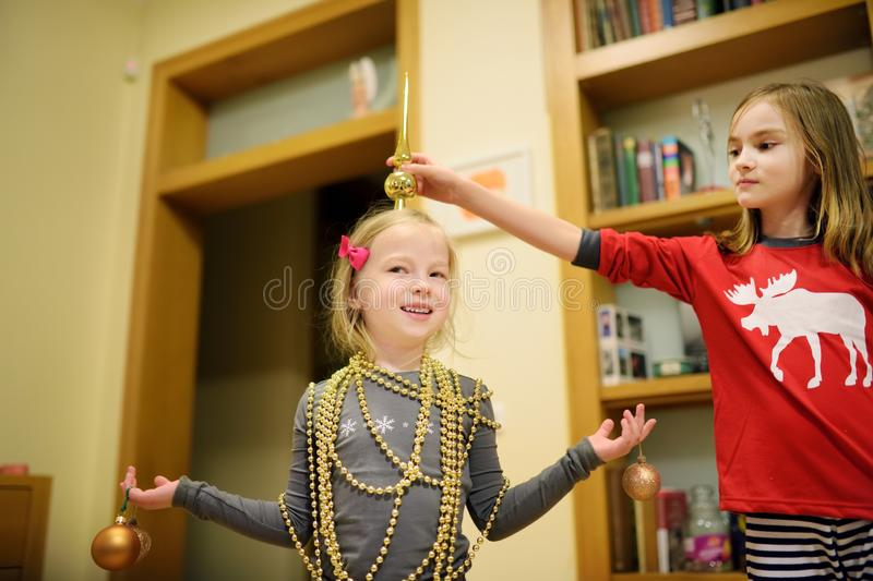 Two adorable sisters decorating a Christmas tree with colorful glass baubles at home. Family leisure at Xmas time. Trimming a fest. Two adorable sisters stock photo