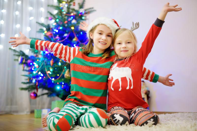Two adorable sisters decorating a Christmas tree with colorful glass baubles at home. Family leisure at Xmas time. Trimming a fest. Two adorable sisters stock photography