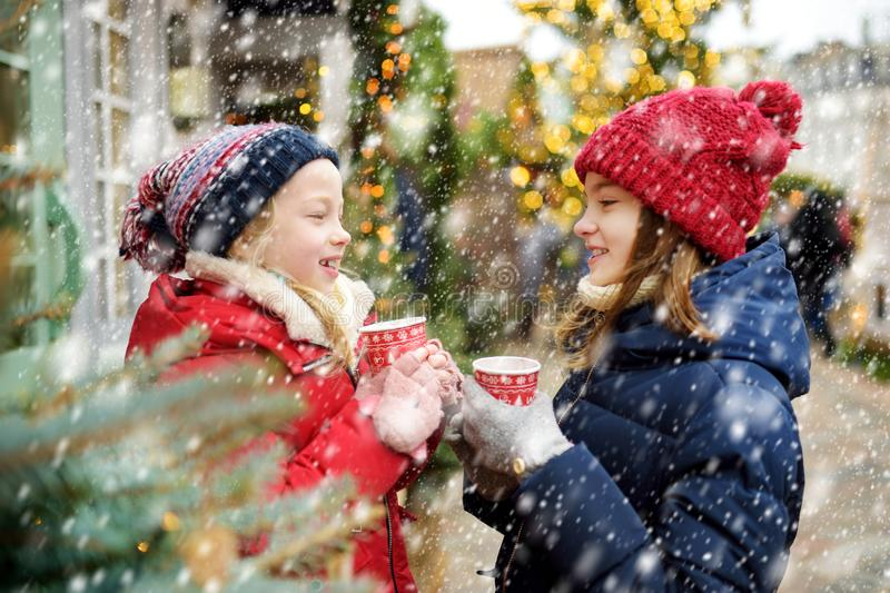 Two adorable sisters drinking hot chocolate on traditional Christmas fair in Riga, Latvia. Children enjoying sweets, candies and royalty free stock photos