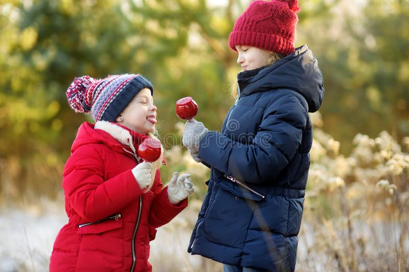 Two adorable sisters eating red apples covered with sugar icing on beautiful sunny Christmas day. Children enjoying sweets, candie stock photography