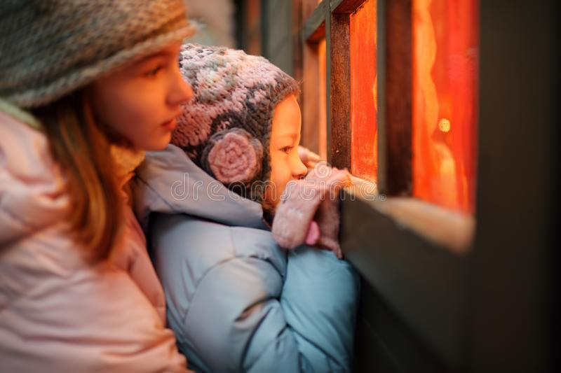 Two adorable sisters having a good time together on traditional Christmas fair in Riga, Latvia. Children enjoying sweets, candies stock photography