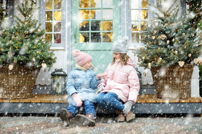 Two adorable sisters having a good time together on traditional Christmas fair in Riga, Latvia. Children enjoying sweets, candies stock photos