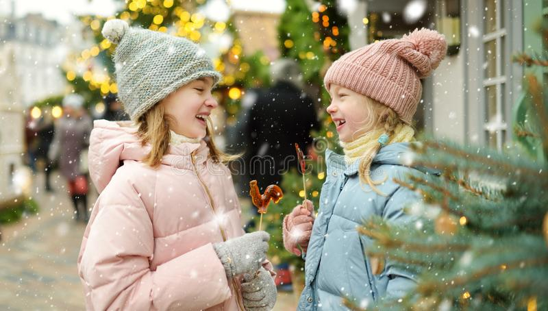 Two adorable sisters having rooster-shaped lollipops on traditional Christmas fair in Riga, Latvia. Children enjoying sweets, stock images