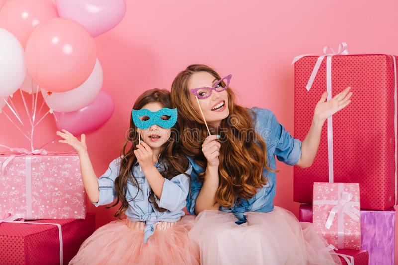 Two adorable sisters wearing funny colorful carnival masks sitting next to present boxes. Family portrait of charming. Young mother and cute lovely daughter royalty free stock photo
