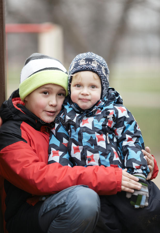 Two adorable young brothers outdoors in winter stock photography