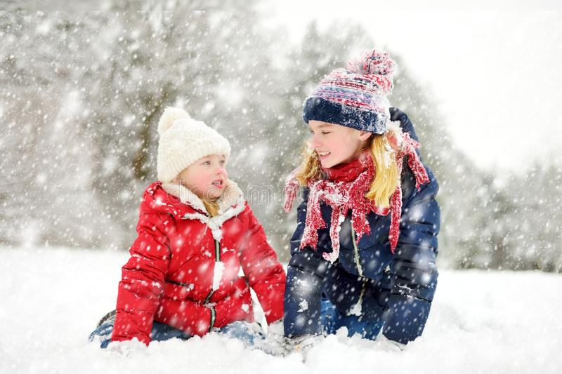 Two adorable young girls having fun together in beautiful winter park. Cute sisters playing in a snow stock image