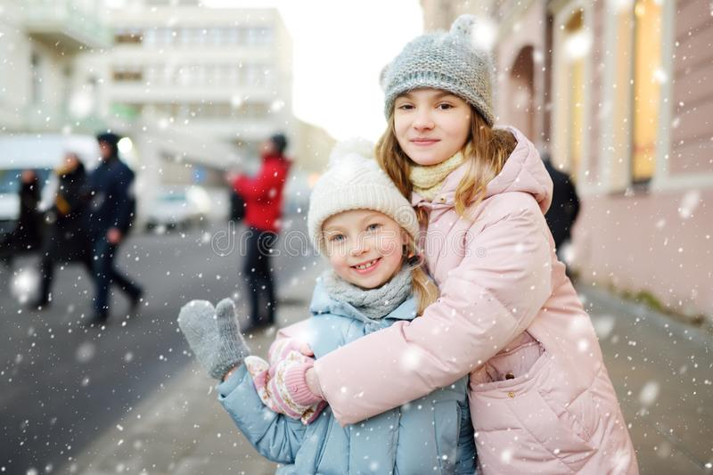 Two adorable young sisters having fun on beautiful winter day in a city. Cute children having a walk in winter town stock photography