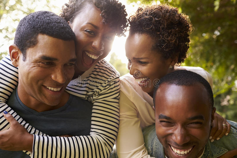 Two adult black couples have fun piggybacking, close up stock photo