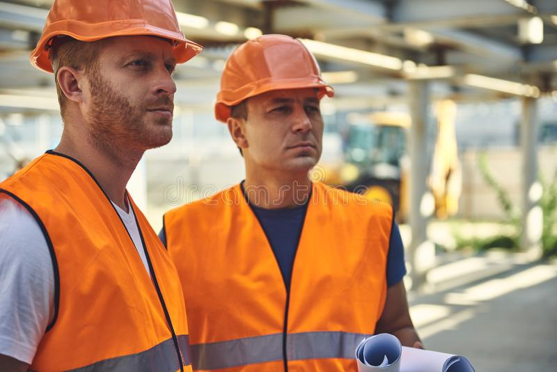 Two adult builders are locating at the construction site royalty free stock images