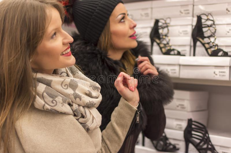 Two adult girls in a shoe store. Two adult girls in the shoe store look around and look for something for themselves royalty free stock image