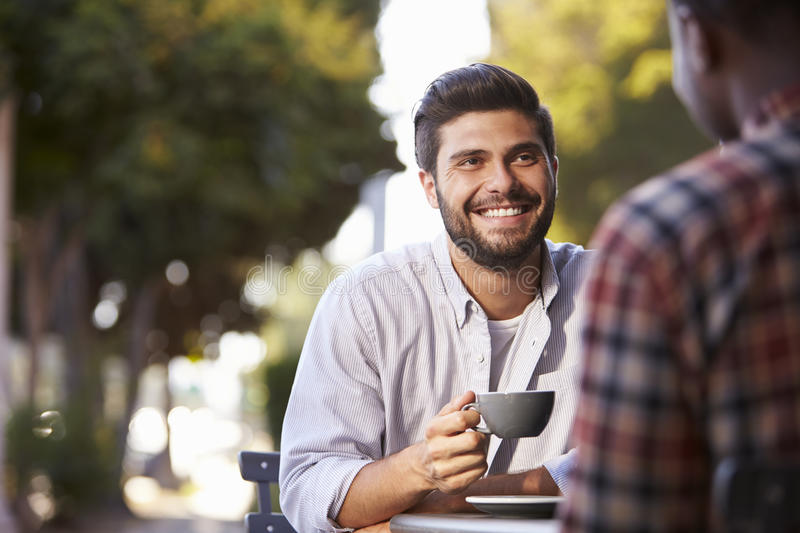 Two adult male friends sit talking over coffee outside cafe stock photo