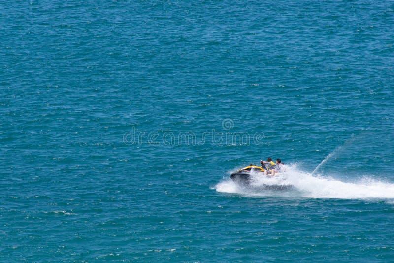 Males Riding Jet-ski at Sea stock photo