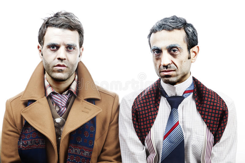 Wannabe Seniors Portrait. Two adult men (mid 30's and mid 20's) wearing old-man clothes and makeup looking at the camera with a sad/numb/exhausted gaze. Isolated stock photos
