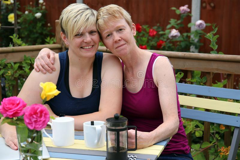 A happy gay couple at home in the garden, and embracing. Two adult middle aged gay women embracing in a garden full of roses on a summer day, smiling, looking royalty free stock photo