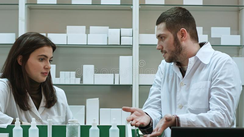 Two adult pharmacists having conflict, discussing problems at pharmacy royalty free stock images