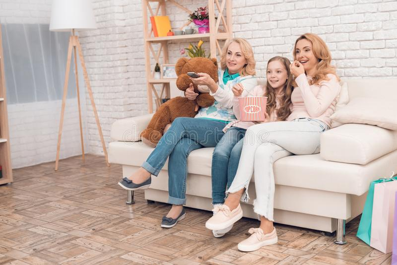 Two adult women and a girl are sitting on the couch and watching TV. royalty free stock photo