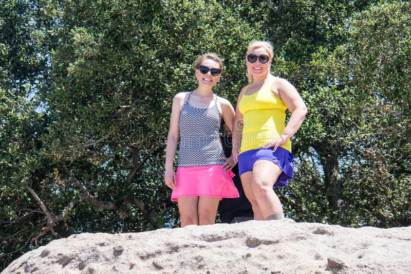 Two adult women hikers stand on the top of a giant boulder, happy, in the sunshine. During a summer day hike royalty free stock photos