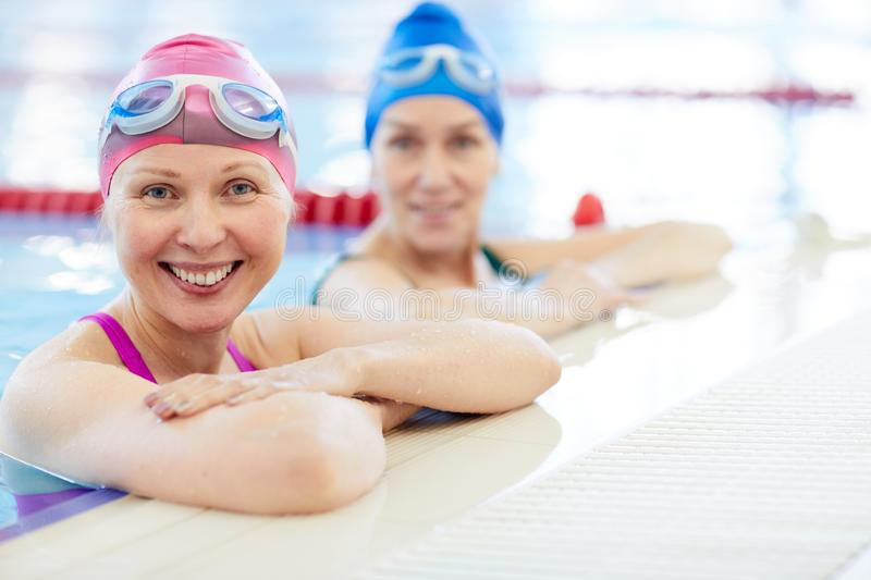 Two Adult Women in Swimming Pool royalty free stock images