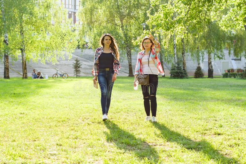 Two adult women walk through the city park at sunset. Two adult women walk through the city park at sunset stock photos