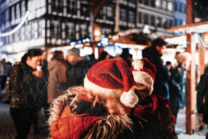Two adult women wearing funny Christmas Hats. Evening city scene with two women wearing red santa hats talking in center of the Christmas Market - side view royalty free stock photography