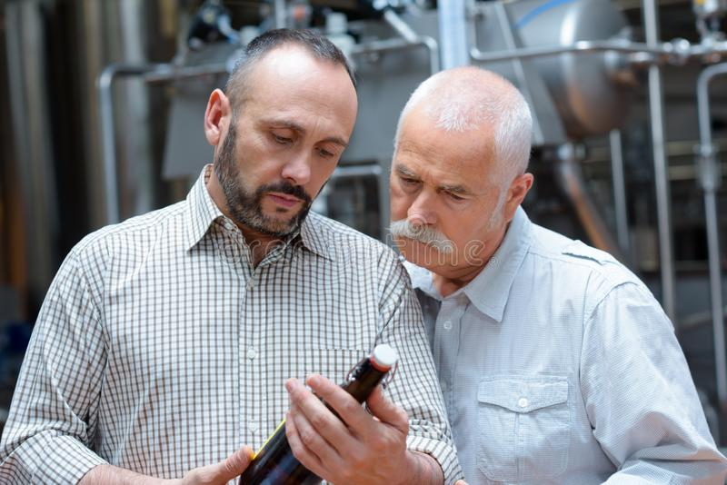 Two adult workers controlling wine bottles royalty free stock photography