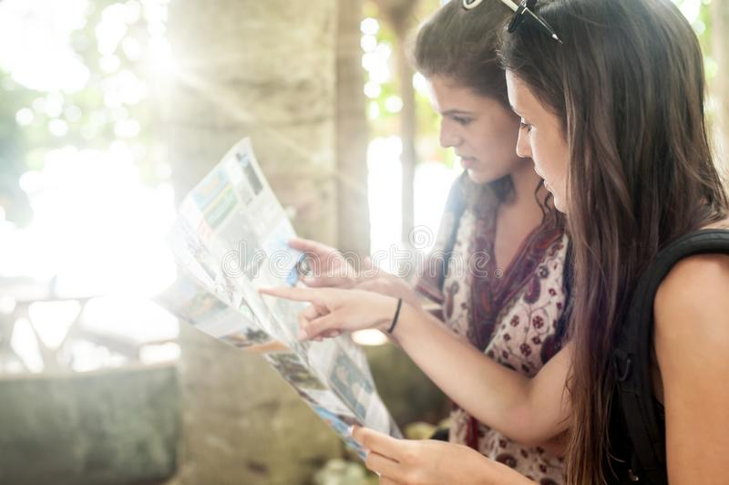 Two adventure traveler woman backpackers looks at tourist map. Two adventure traveler women backpackers looks at tourist map. Summer holiday outdoor vacation stock image
