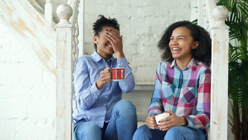 Two african american curly girls sistres sitting on stairs have fun laughing and chatting together at home stock image