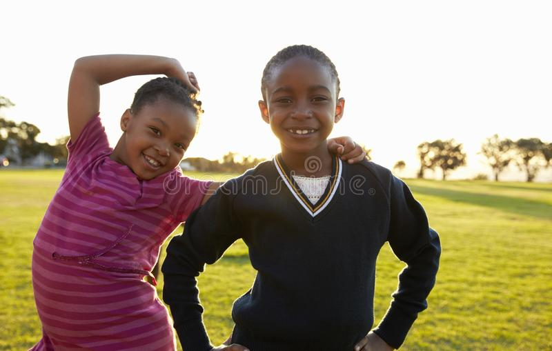 Two African elementary schoolgirls pose to camera in a field stock image