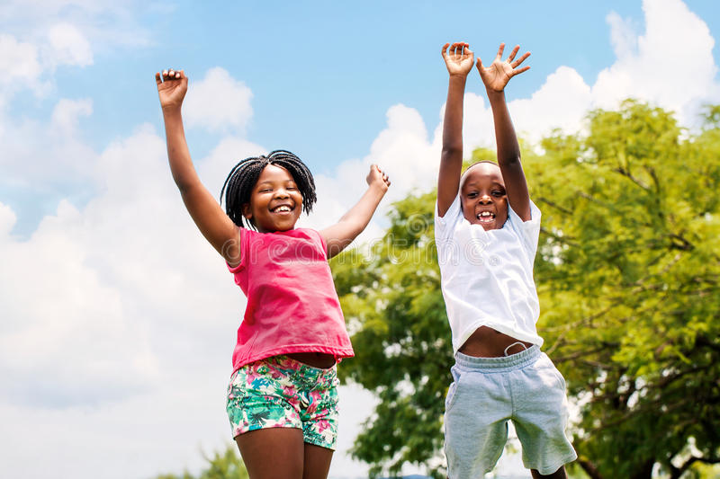 Two African kids jumping in park. Action portrait of young African boy and girl jumping in park royalty free stock photo