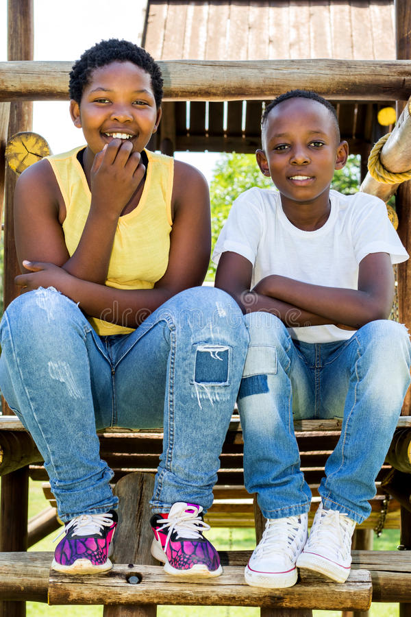 Two african kids sitting on wooden structure in park. royalty free stock photography