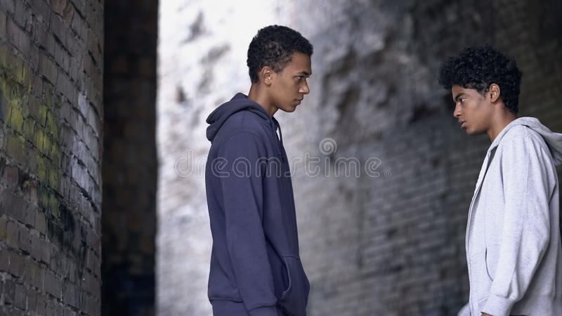 Two afro-american teenagers looking at each other, confrontation concept stock photos