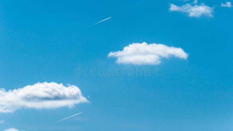 Two Airliners on the horizon fly out of the clouds. two tracks from the running engines of aircraft. Clear blue sky and clouds. travelling by plane. air flight stock image