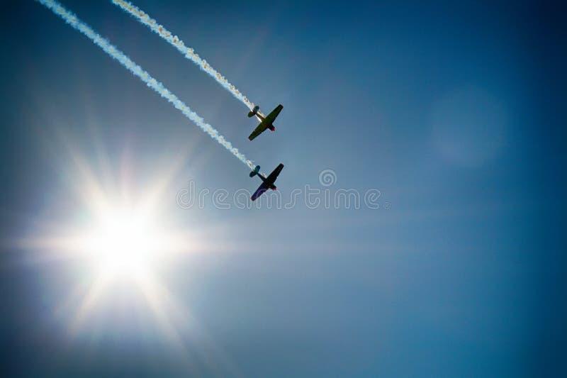 Two Airplane Flying Under Blue Sky Emitting White Smoke stock photography