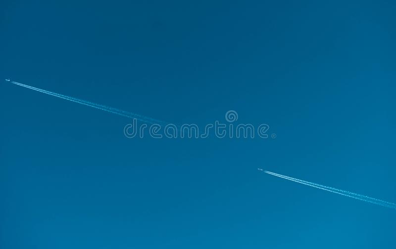 Two airplane with white condensation tracks. Jet plane on clear blue sky with vapor trail. Travel by aeroplane concept. Trails royalty free stock image