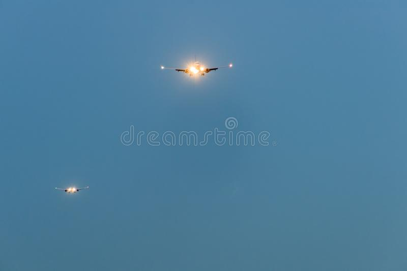 Two airplanes in the blue sky at night with headlight. Toward to the front stock photos