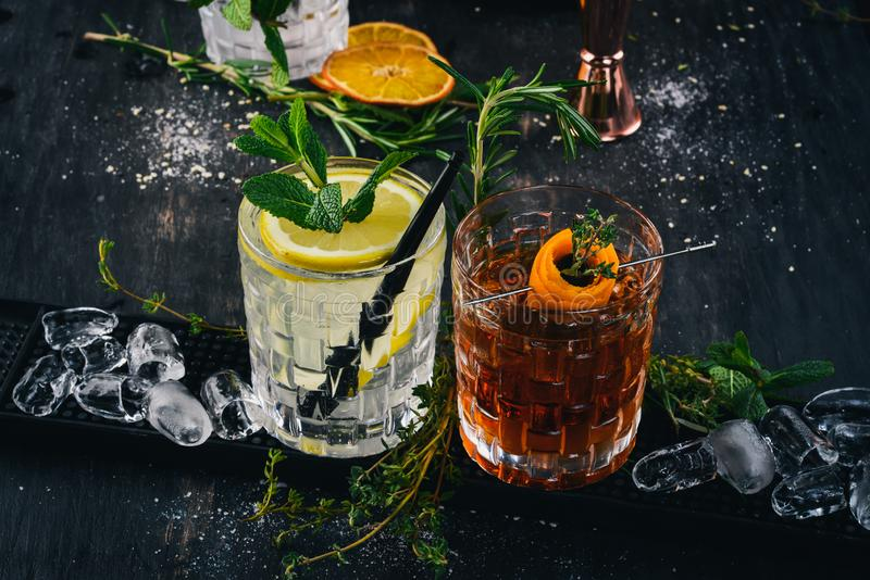 Two Alcoholic Cocktail Gin and Tonic, Negroni. On a black wooden background stock photos
