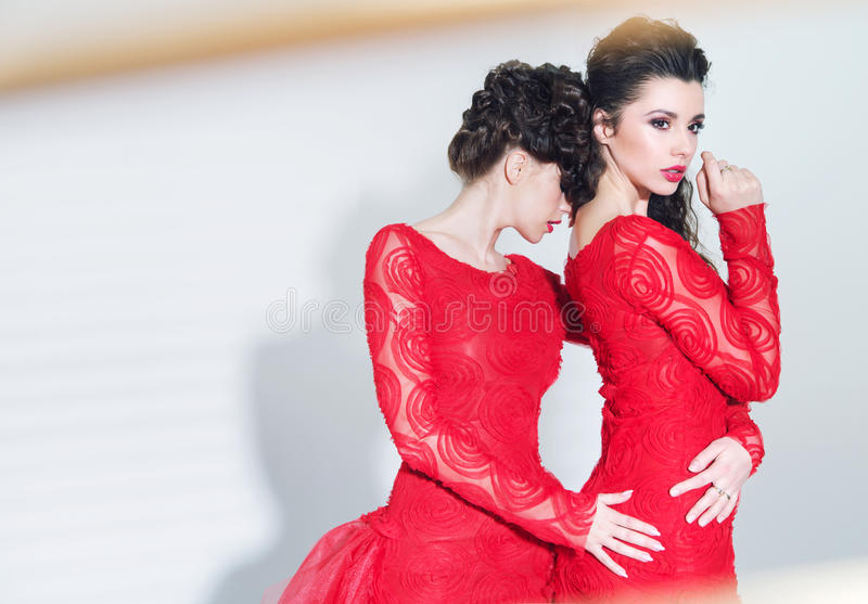 Two alluring women wearing great dresses royalty free stock images