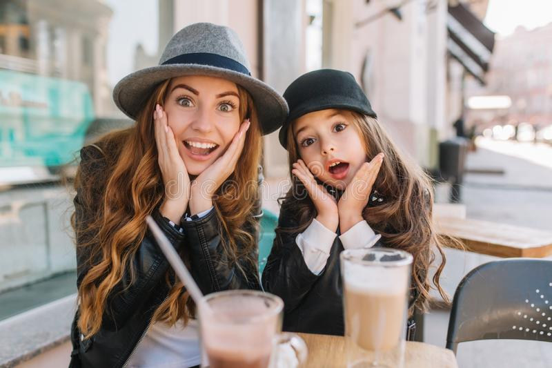 Two amazing girls in trendy hats posing with funny face expression during lunch in street restaurant in sunny day. Young. Women with light-brown hair fooling royalty free stock photography