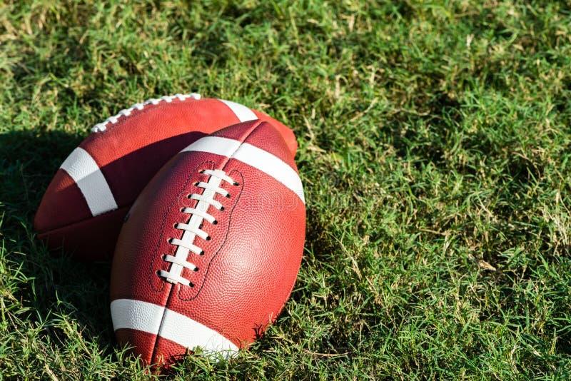 Two American College High School Junior Football on Grass. Two American college high school junior striped footballs on green grass football field stock photos