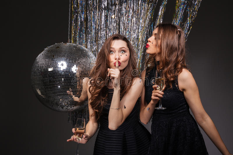 Two amusing women showing silence gesture and drinking champagne royalty free stock image