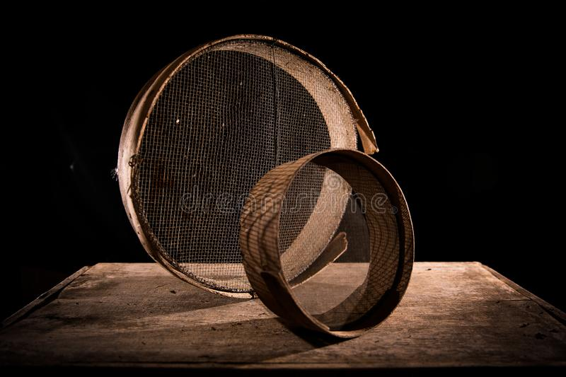 Two ancient sieves on a wooden table. Two old and shabby sieves in the center of the photo on a wooden table with a black background royalty free stock images