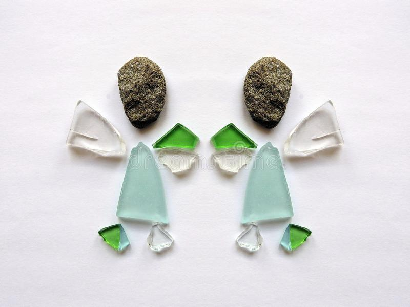 Two angels made from glass pieces and stone stock photography