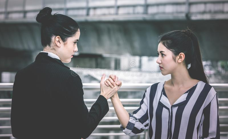 Two angry business woman arm wrestling conflict. Two angry business women with arm wrestling conflict stock photography