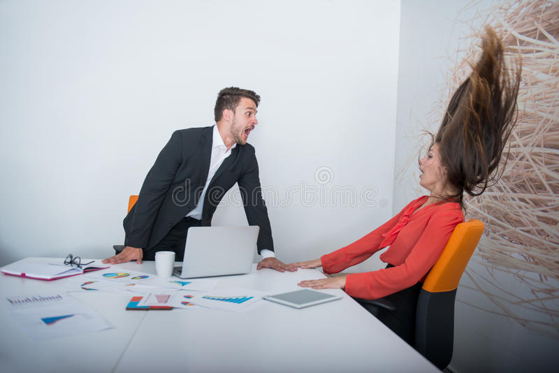 Two angry businesspeople arguing furious showing a negative growth graph. At office royalty free stock photo