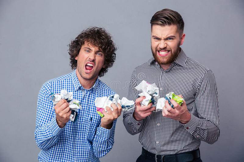 Two angry men with crumpled paper royalty free stock image