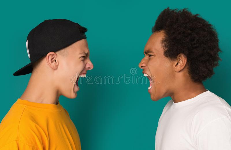 Two angry teens shouting at each other. Interpersonal conflict. Two angry teens yelling, shouting at each other blaming for problems on blue background royalty free stock images