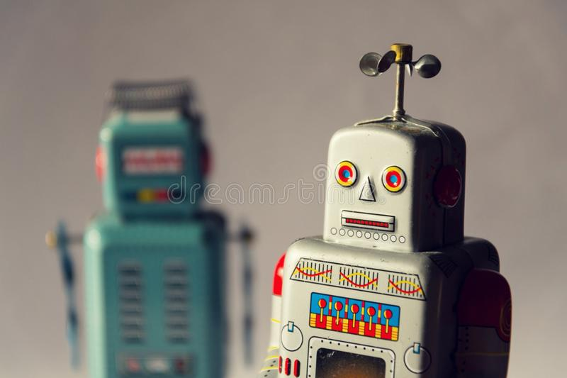 Two vintage tin toy robots, robotic delivery, artificial intelligence concept royalty free stock photos