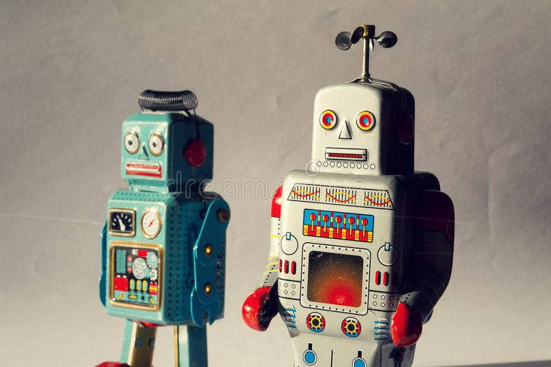 Two angry vintage tin toy robots, artificial intelligence, robotic drone delivery, machine learning concept royalty free stock images