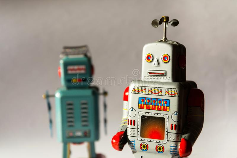 Two angry vintage tin toy robots, artificial intelligence, robotic drone delivery, machine learning concept. Two angry vintage tin toy robots, artificial stock images
